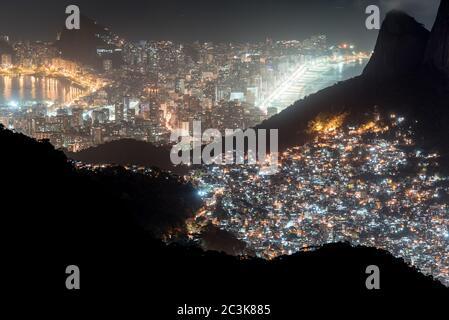 Nachtansicht oder Favela Rocinha im Berg und Ipanema Bezirk hinter in Rio de Janeiro, Brasilien. - Stockfoto