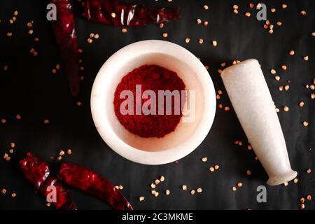 Flache Lage von getrockneten und zerkleinerten roten Chili-Pfeffer oder Chili Cayennepfeffer Pulver in Steinmörtel mit Stößel und Chili-Samen isoliert auf schwarzem Hintergrund.