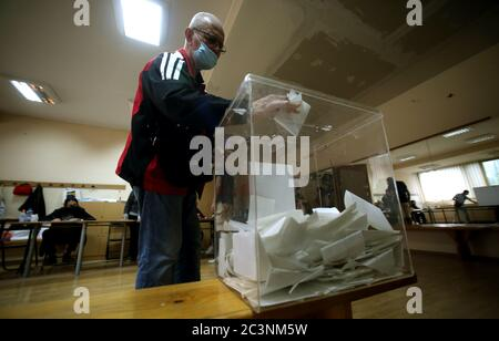 Belgrad, Serbien. 21. Juni 2020. Ein Mann mit einer Gesichtsmaske, der in einem Wahllokal abstimmt. Die Wähler der westlichen Balkanstaaten wählen ihre Vertreter in der Nationalversammlung mit 250 Sitzen. Die Abstimmung war ursprünglich für den 26. April geplant, wurde jedoch aufgrund des Ausnahmezustands verschoben, der in einem Versuch erklärt wurde, die Ausbreitung der anhaltenden Pandemie der COVID-19-Krankheit, die durch das SARS-CoV-2-Coronavirus verursacht wurde, einzudämmen. Quelle: Koca Sulejmanovic/Alamy Live News - Stockfoto