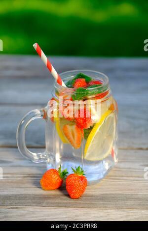 Glas Sommergetränk mit Erdbeere, Zitronenscheiben und Minze. Erfrischender Cocktail, selbstgemachter Detox-Punsch, kalte Limonade. - Stockfoto