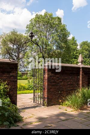 Eine Ziegelmauer mit schmiedeeisernem Zaun Eingang in den Garten im Mellon Park an einem Sommertag, Pittsburgh, Pennsylvania, USA - Stockfoto