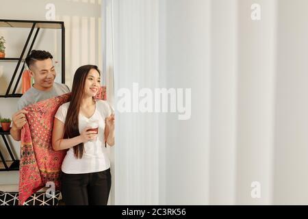 Lächelnder, nachdenklicher junger Mann, der seiner hübschen Freundin warme Decke bringt, heißen Tee trinkt und durch das Fenster schaut - Stockfoto