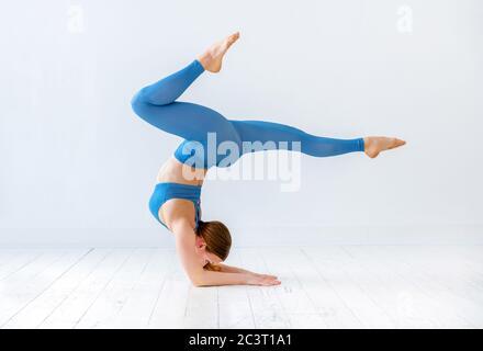 Sportliche Frau beim Ellbogenständer Yoga-Pose mit ausgestreckten Beinen in Seitenansicht gegen eine weiße Wand in einem Gesundheits- und Fitnesskonzept - Stockfoto