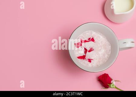 Tasse Rose Cardamom Almond Moon Milk (rosa Mondmilch) auf pastellrosa Hintergrund. Overhead-Ansicht mit Platz für Text Stockfoto