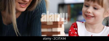 Mutter und Tochter sitzen am Tisch Spiel spielen