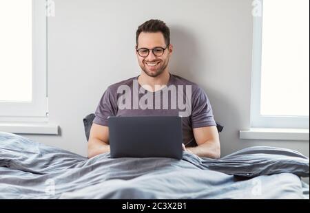 Mann Mit Laptop Online Von Zu Hause Aus Sitzen Im Bett - Stockfoto