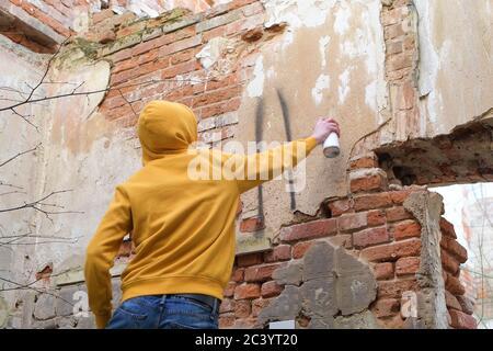 Ein junger Mann zieht an die Wand eines verlassenen Gebäudes. Teen verwendet Sprühfarbe