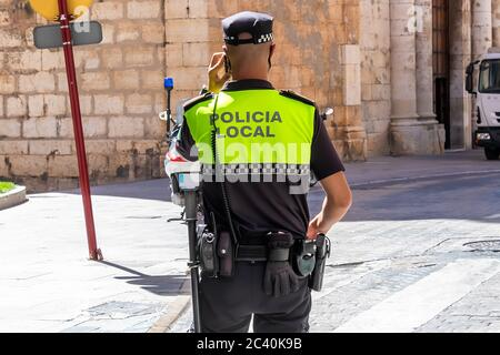 """Rückansicht der spanischen Polizei mit Logo """"Local Police"""" auf Uniform Aufrechterhaltung der öffentlichen Ordnung in den Straßen von Jaen, Spanien - Stockfoto"""