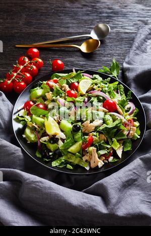 Salat mit gezupftem Hühnerfleisch, Oliven, roten Zwiebeln, Tomaten, Gurken, Minze, Salat, bestreut mit zerbröseltem Feta-Käse in einer schwarzen Schüssel, vertikale Ansicht
