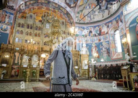 Snagov, Rumänien - 21. Juni 2020: Ältere Frau mit Covid-19 Maske betet vor einer orthodoxen christlichen Kirche.