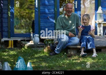 Glücklicher Großvater und Enkelin mit Himbeeren auf ihren Fingerspitzen sitzen auf der Terrasse im Garten - Stockfoto