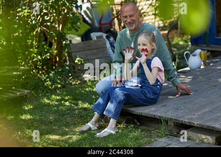 Großvater und Enkelin mit Himbeeren auf den Fingerspitzen sitzen auf der Terrasse im Garten - Stockfoto