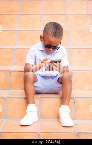 Portrait von kühlen kleinen Jungen trägt Sonnenbrille auf Treppen im Freien mit Handy sitzen - Stockfoto
