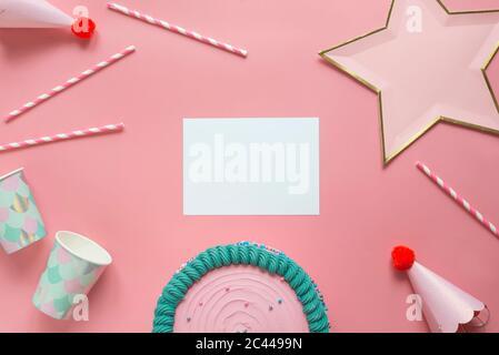 Studio-Aufnahme von Geburtstagskuchen, leeres Stück Papier, Trinkhalme, Einweg-Tassen, Party-Hüte und sternförmige Dekoration