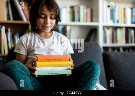 Junge sitzt auf der Couch zu Hause halten Stapel von vier Büchern Stockfoto
