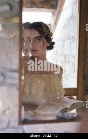 Junge Frau im Hochzeitskleid mit Buch Blick auf Spiegel - Stockfoto