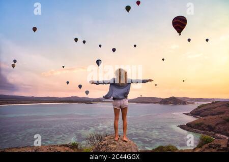 Indonesien, West Nusa Tenggara, Heißluftballons fliegen über einfarbige Frau, die auf felsigen Küsten mit erhobenen Armen steht - Stockfoto