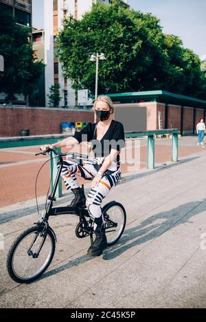 Junge Frau trägt Gesichtsmaske während Corona Virus, Radfahren auf Faltrad. - Stockfoto