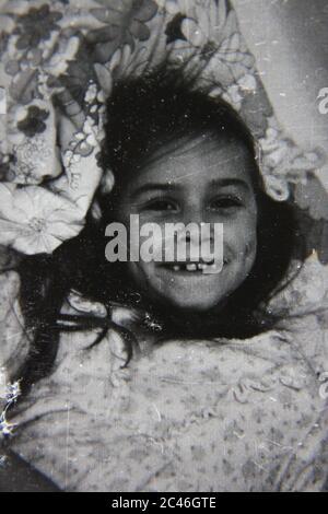 Feine 70er Jahre Vintage schwarz-weiß Lifestyle-Fotografie von einem jungen Mädchen posiert für die Kamera. - Stockfoto