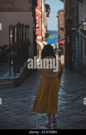 Junge hübsche Frau im gelben Kleid zu Fuß durch die kleinen Straßen der Stadt Porec Meer auf Hintergrund - Stockfoto