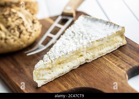 Brie-Käse. Weißer Weichkäse mit weißer Form auf Schneidebrett. - Stockfoto