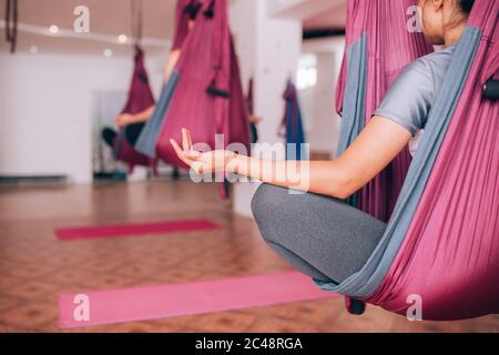 Schöne junge Mädchen, die Fliegenyoga auf Hängematten tun, meditieren auf Hängematten, Gesundheitspflege - Stockfoto