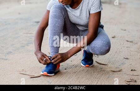 Junges Mädchen in Sportswear hockt auf einer Strecke und bindet ihre Schnürsenkel für den Sport. - Stockfoto
