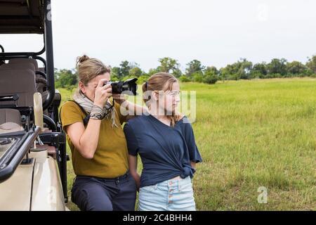 Mutter fotografiert mit Teenager-Tochter in der Nähe von Safari-Fahrzeug, Botswana - Stockfoto