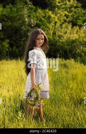 Das Mädchen steht im grünen Gras, sie hat einen Blumenkranz gemacht.