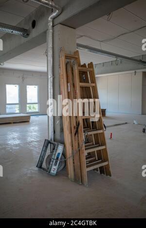 Holzleitern, die an einer Säule in einem Fabrikgebäude auf einer Baustelle gelehnt sind - Stockfoto