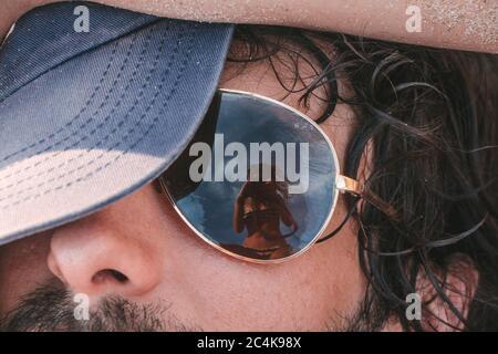 Spiegelung einer Frau in der Sonnenbrille eines Mannes, während sie ein Foto macht