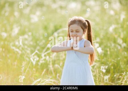 Kleines Mädchen bläst Seifenblasen im Sommer auf einem Spaziergang - Stockfoto