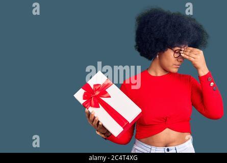 Junge afroamerikanische Mädchen halten Geschenk müde reiben Nase und Augen Gefühl Müdigkeit und Kopfschmerzen. Stress und Frustration Konzept. - Stockfoto