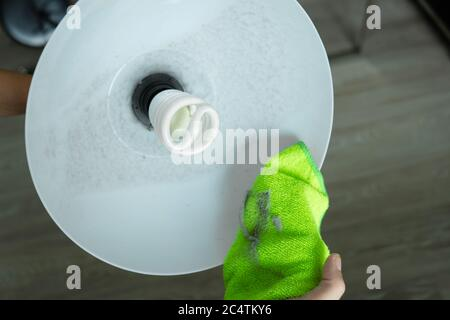 Reinigung des Hauses. Wischen Sie den Staub mit einem grünen Lappen von der Stehleuchte ab. Energiesparlampe. Viel Staub - Stockfoto