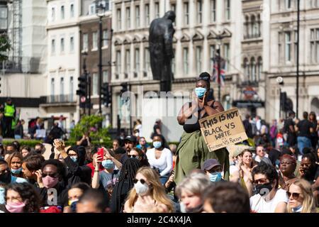 Eine Protesterin steht unter einer Menschenmenge, die während einer Demonstration von Black Lives Matter klatscht, Parliament Square, London, 21. Juni 2020