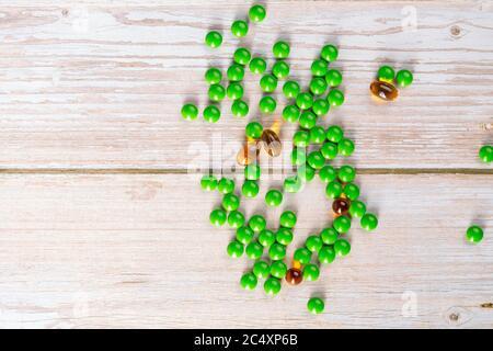 Heimtherapie. Runde grüne Vitamintabletten auf Holztisch - Stockfoto