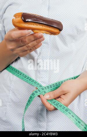 Diät-Konzept. Junge Frau mit Schokoladeneclair Messung ihrer Taille mit Maßband auf weißem Hintergrund - Stockfoto