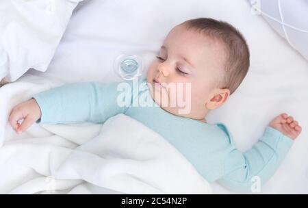Baby schläft mit einem Schnuller zur Seite. Hellblauer Pyjama und weiße Bettwäsche. - Stockfoto