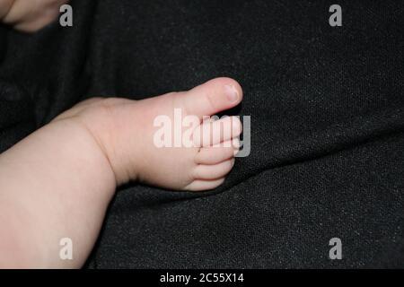 Neugeborener Enkelbaby auf schwarzem Hintergrund.
