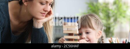 Mama hilft ihrer Tochter geduldig beim Aufbau von Strukturen