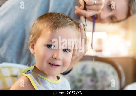 Close-up junge Erwachsene kaukasische Mutter machen Haarschnitt fot niedlich liebenswert Sohn Kleinkind Junge zu Hause durch Quarantäne und Sperrung. Mutter schneiden Haare des Kindes