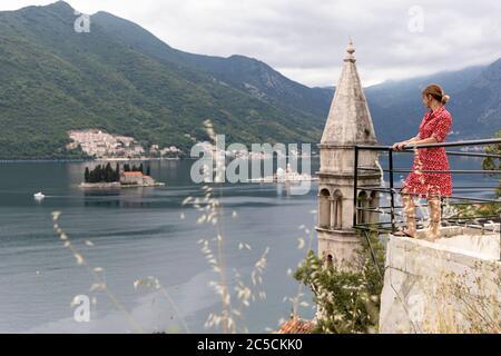 Frau in rotem Kleid steht am Zaun am Aussichtspor mit Panoramablick auf die historische Stadt Perast an der berühmten Bucht von Kotor, Montenegro