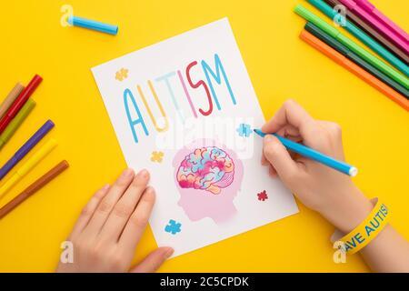 Zugeschnittene Ansicht der Frau Zeichnung Karte mit Kopf, Gehirn und Puzzle für Autismus Awareness Day auf gelb - Stockfoto