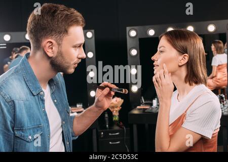 Seitenansicht des Modells zeigt auf Wange in der Nähe Make-up Künstler hält kosmetischen Pinsel in Fotostudio - Stockfoto