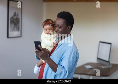 Afrikanisch lächelnder Vater hält ein Mädchen auf den Händen und benutzt sein Handy zu Hause - Stockfoto