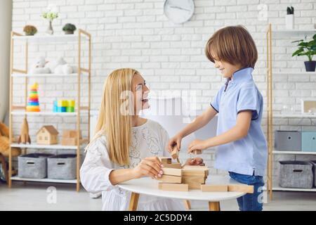 Schöne junge Mutter spielen Brettspiel mit ihrem Sohn zu Hause. Eltern- und Kinderbauturm aus Holzbaublöcken