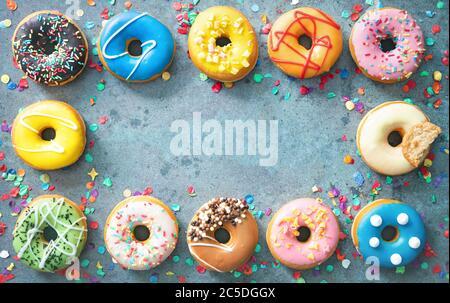 Festlicher Karnevals- oder Geburtstagsrahmen aus verschiedenen bunten Donuts mit Konfetti auf rotgrauem Hintergrund - Stockfoto
