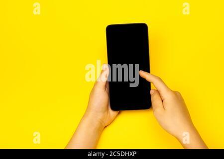 Smartphone in Kinderhand auf der gelben Backstage. Das Konzept der notwendigen Dinge eines kleinen Mädchens, Technik für Kinder. Flach liegend, Kopierplatz. - Stockfoto