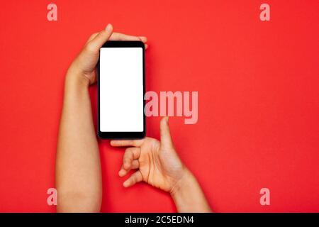 Smartphone in Kinderhand auf rotem Hintergrund. Das Konzept der digitalen, notwendigen Dinge eines kleinen Mädchens, Technologie für Kinder. Flach liegend, Kopierbereich, isoliertes weißes Display. - Stockfoto