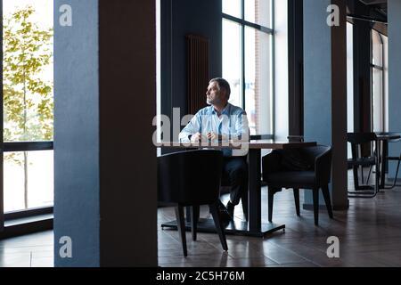 Nachdenklicher Geschäftsmann, der Kaffee im Café trinkt und wegschaut. - Stockfoto